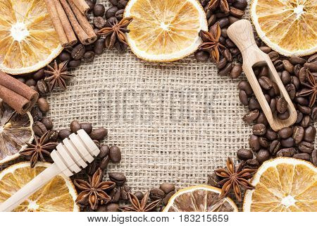 orange slices with coffee beans, spices and honey dipper on canvas background. Image with copy space