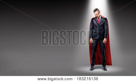 A sad businessman wearing a red superhero cape standing in the spotlight with his shoulders slumped. Public scrutiny. Business results. Loss and failure.