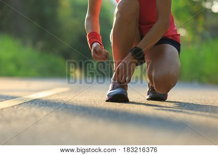 Young fitness woman tying shoelace on morning tropical forest trail