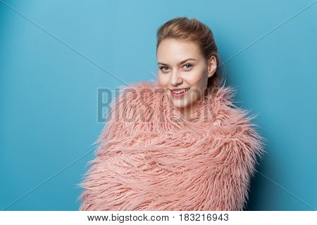 Portrait of beaming female expressing coziness. She bundling warm wrap up. Comfort concept. Copy space
