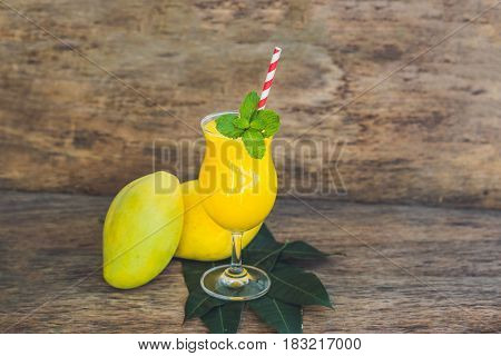 Juicy Smoothie From Mango In Glass With Striped Red Straw And With A Mint Leaf On Old Wooden Backgro