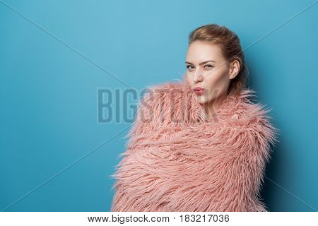 Portrait of half length perky woman winking at camera. Lady covering wool blanket. Copy space