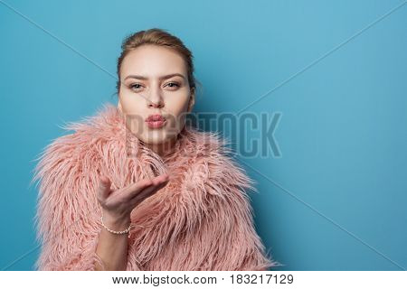Portrait of young female expressing dreaminess. She sending air kiss. Copy space