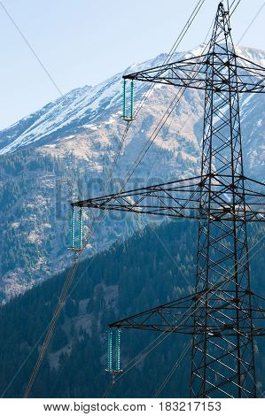 Mountain power line. High-voltage tower on sky and mountain background in Austria