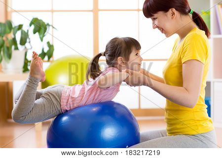 child doing gymnastic on fitness ball with mother at home