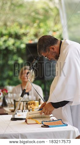 Quito, Pichincha / Ecuador - April 22 2016: Catholic priest giving Mass outdoors in the garden of a house
