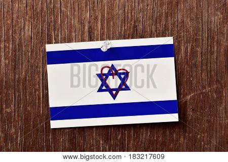 closeup of a flag of israel with a heart drawn in it pinned with a push-pin to a rustic wooden background