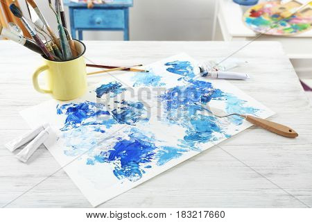 Colorful abstraction created with oil paint strokes and painter's tools on white wooden table