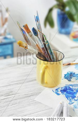 Metal mug with brushes and palette knives on painter's working table