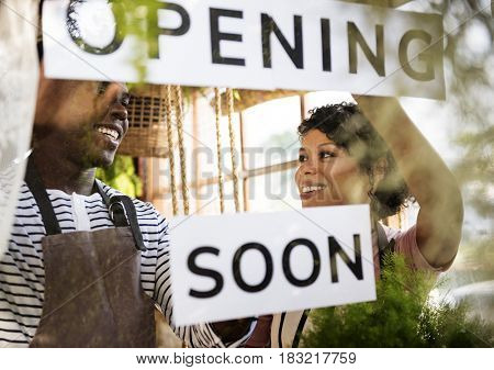 Couple Showing Opening Soon Paper Sign