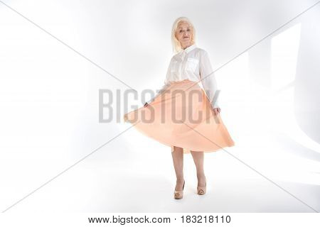 Young soul. Full length portrait of happy smiling mature lady is standing and looking at camera with superiority. Isolated. Copy space