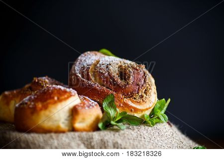Sweet bun with nut filling in powdered sugar on a black background