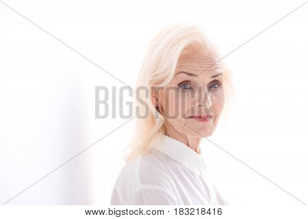 Wisdom of years. Tranquil mature lady is looking at camera with light smile. Copy space. Isolated