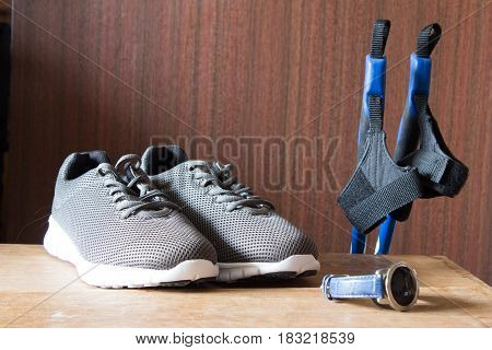 Gray sport shoes with Nordic Walking sticks and chronometer. Pair of sneakers on wooden background