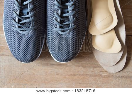 Gray sport shoes with orthopedic insoles. Wooden background.