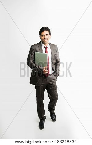 Portrait of Confident indian young businessman working on his computer or laptop in the office, Businessman using a laptop computer and smiling standing isolated over white background