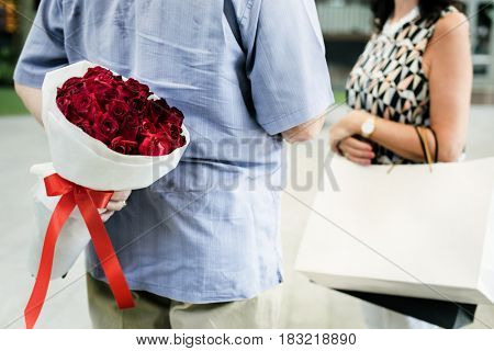 Guy hiding a bouquet of flowers behind his back