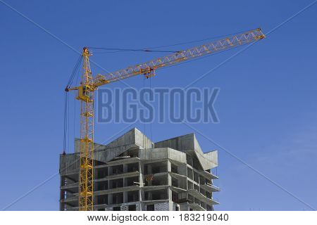 Tower crane and reinforced building under construction project site against blue sky