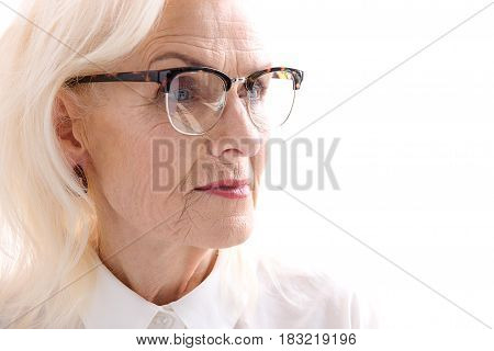 Confident mature woman in glasses is looking aside with determination. Isolated. Copy space. Portrait