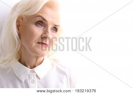 Serious old woman is looking aside with thoughtful facial expression. Isolated. Copy space. Portrait