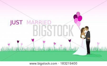 Just married - wedding. Bridal couple in a field full of heart flowers and with balloons.
