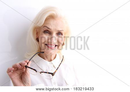 Cheerful mature lady is holding glasses and looking at camera with bright smile. Isolated. Portrait. Copy space