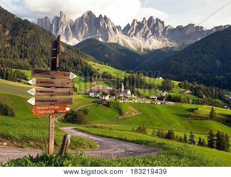 evening panoramic view of Geislergruppe or Gruppo dele Odle from Saint Magdalena with tourist sign post Italian Dolomites Alps mountains