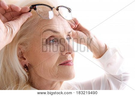 Curious mature woman is taking off her eyewear and pensively looking aside. Isolated. Portrait