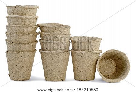 a row of jars cups of peat for seedlings of plants inserted into one another and are installed in a row isolated on white background