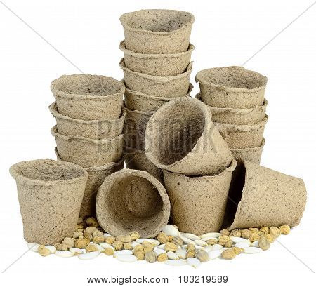 a bunch of pitchers cups of peat for seedlings of plants inserted into one another and standing in a row on the table seeds of nasturtium pumpkin and zucchini isolated on white background