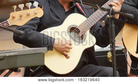 Detail of the hand of an artist dressed in black playing the strings of an acoustic guitar at a party