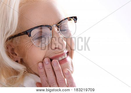 Cheerful mature woman in glasses is brightly smiling with closed eyes. Isolated. Copy space. Portrait