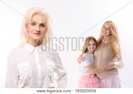 Curious old woman is standing afore her daughter and granddaughter. They are hugging each other. Isolated. Portrait