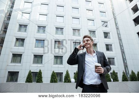 Young handsome busy man talking on phone in business center