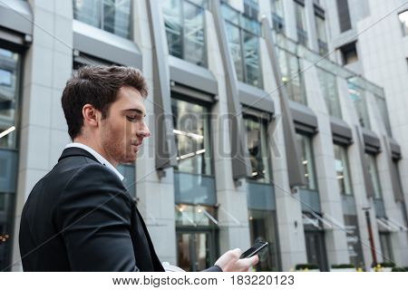Busy serious man with smartphone in large building