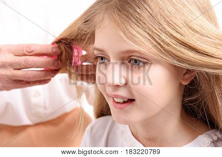 Portrait of cheerful girl is looking aside with curiosity in her eyes. Old woman using curler. Focus on youthful face