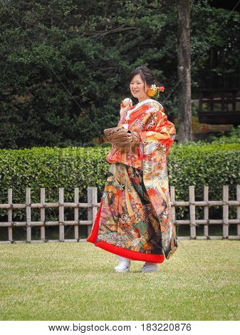 Korakuen Garden, Okayama, Japan - April 8, 2017 : Bride in kimono enjoying baseball in Cherry blossoms festival in park. Hanami is Japanese tradition of welcoming spring.