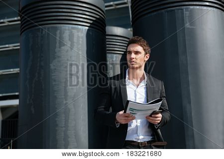 Serious handsome businessman holding documents and looking away in the street