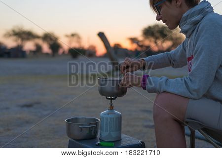 Woman cooking with gas stove in camping site at dusk. Gas burner pot and smoke from boiling water. Adventures in african national parks.
