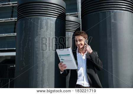 Young busy man talking on phone about documents in the street