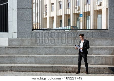 Full-length of businessman holding folder standing near stairs in the street