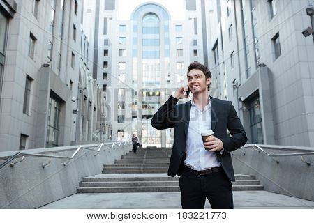 Smiling businessman holding coffee and talking on phone while walking