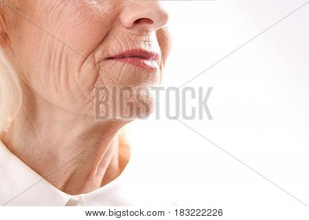 Close up of wrinkled face of matured lady. Focus on chin. Isolated. Copy space