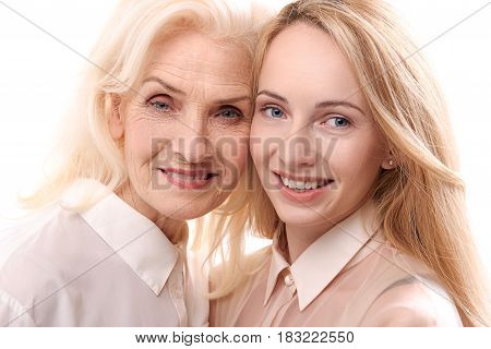 Mother and daughter are standing together and looking at camera with smile. Portrait