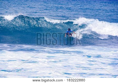 BASSE POINTE MARTINIQUE - APRIL 22 2017. An unidentified man surfs on waves during the surf championship in Martinqiue. Bleue sea white waves sport competition.