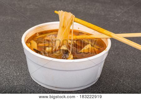 Spicy soup with rice noodles and tofu cheese. Studio Photo