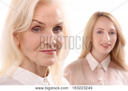 Mature lady is standing ahead her daughter. They are looking at camera with interest. Portrait