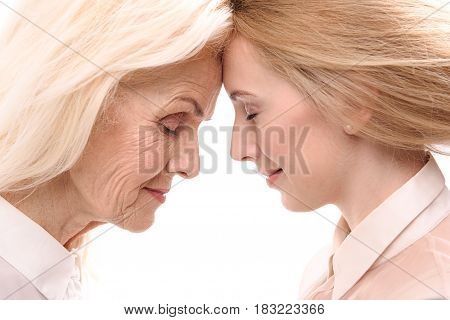 Unity with heart of mother. Young daughter is standing afore her mom. They are smiling. Isolated