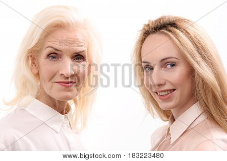 Cheerful mother and daughter are standing together and looking at camera with smile. Portrait. Isolated