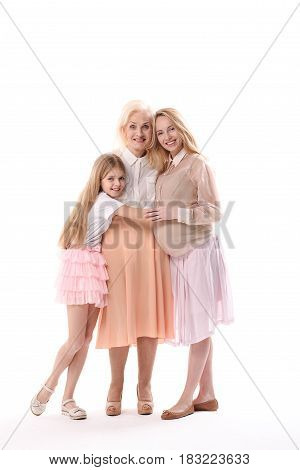 Pregnant mother with her daughter are hugging eldest lady in their family. They are looking at camera with bright smile. Isolated. Portrait